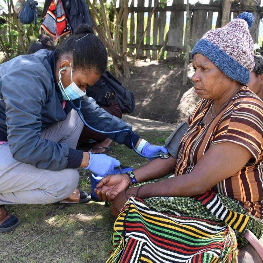 A volunteer checks the health of a woman.